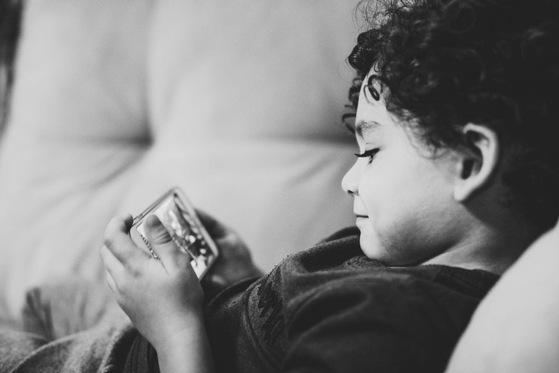 スマホで動画を見ている少年