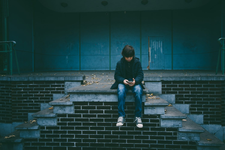 子供が一人でスマートフォンを触っている